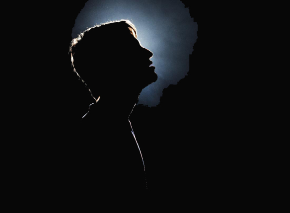 Silhouette of young man looking up.
